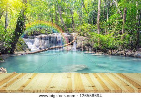 Scenery of Erawan waterfall with wood floor.