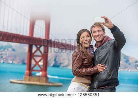 Couple tourists taking selfie photo in San Francisco by Golden Gate Bridge. Interracial young modern couple using smart phone by famous american landmark. Asian woman, Caucasian man.
