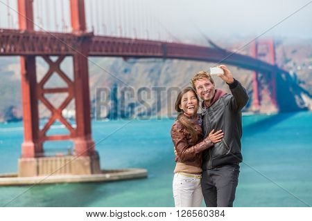 Happy young couple tourists taking selfie in San Francisco by Golden Gate Bridge, USA. Interracial young modern couple using smart phone. Asian woman, Caucasian man.