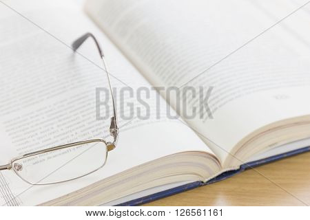 Close Up Glasses And Open Book On The Desk
