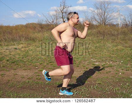 Fat Man Running Outdoors On Nature.