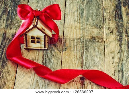 plywood little house with red silk ribbon on old wooden table