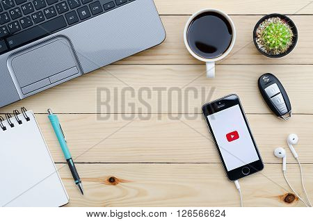 CHIANGMAI THAILAND -JANUARY 252016:Apple iPhone 5S with YouTube app on the screen lying on desk with headphones. YouTube is the popular online video-sharing website founded in February 14 2005