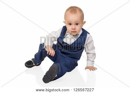 Portrait of a cheerful boy in a strict suit sitting and lean a hand on the floor isolated on white background