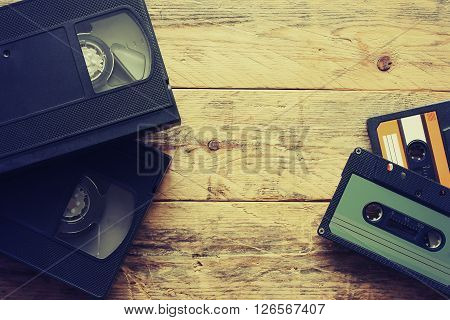 video cassettes and audio cassettes on a wooden table retro style