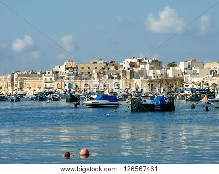 Traditional Maltese fishing boats with reflection on Aug 29,2015 in maltese village MARSAXLOKK