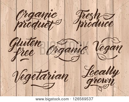 Retro styled healthy food letterings. Label, logo template stylized with stamp effect on a wooden background. Organic, organic product, gluten free, vegan, locally grown, vegetarian, fresh produce. Eps 10 vector. Texture can be easily removed.