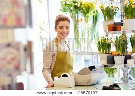 people, business, sale and floristry concept - happy smiling florist woman at flower shop cashbox