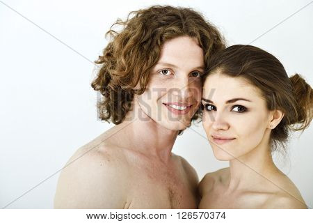 Portrait of young contented couple. Young man and woman embracing each other and happy smiling, studio shot. Psychology of relations, heterosexual couple, intimate family questions, sex life concept.