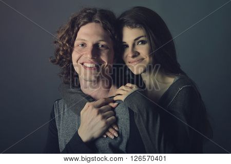Portrait of young contented couple. Young man and woman embracing each other, studio shot. Psychology of relations, heterosexual couple, tenderness, feeling, caress concept. Image toned.
