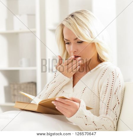 Beautiful woman yawning while reading a book in the morning.