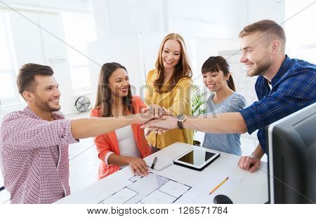 business, startup, architecture, gesture and people concept - happy international creative architect team or students with blueprint putting hands on top together at office