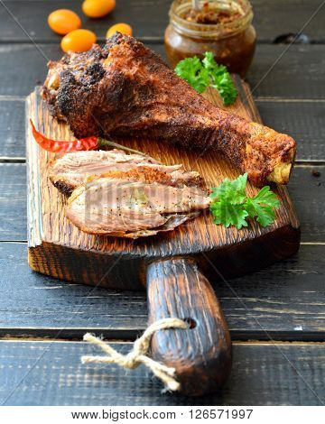 Roast turkey drumstick on a dark wooden table with tomatoes, herbs and spicy sauce