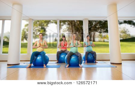 pregnancy, sport, fitness, people and healthy lifestyle concept - group of happy pregnant women exercising on ball in gym over natural window view background