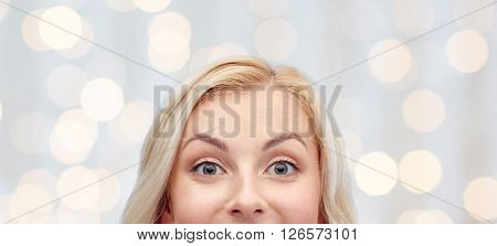 curiosity, advertisement and people concept - happy young woman or teenage girl face over holidays lights background