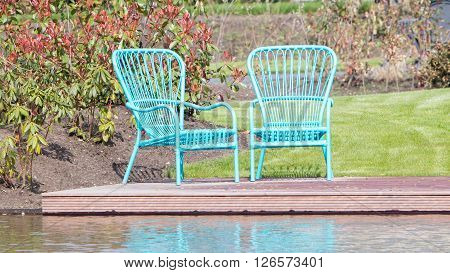 Two blue chairs at the waterfront dutch garden