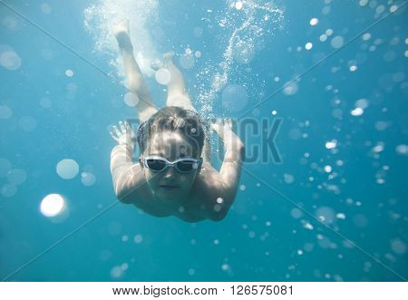 The boy dived into the sea and swimming under water at the viewer