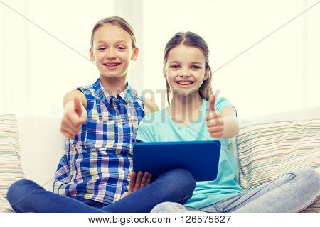 people, children, gesture, friends and friendship concept - happy little girls with tablet pc computer sitting on sofa and showing thumbs up at home