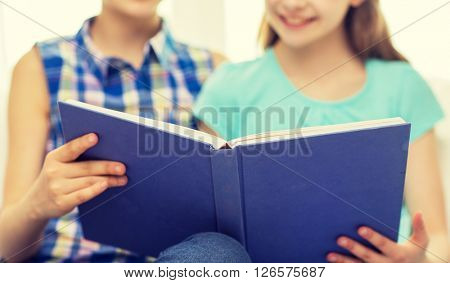 people, children, friends, literature and friendship concept - close up of two happy girls sitting on sofa and reading book at home