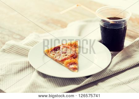 fast food, italian kitchen and eating concept - close up of pizza slice with cup of coca cola drink on wooden table