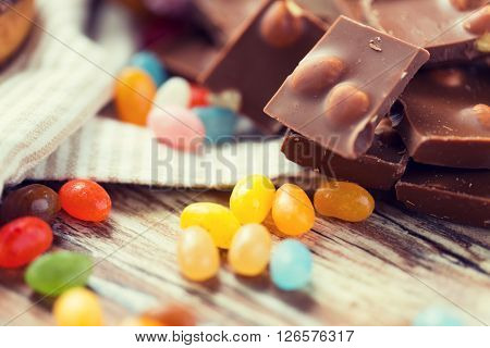 food, junk-food, culinary, baking and eating concept - close up of jelly beans candies and chocolate on table