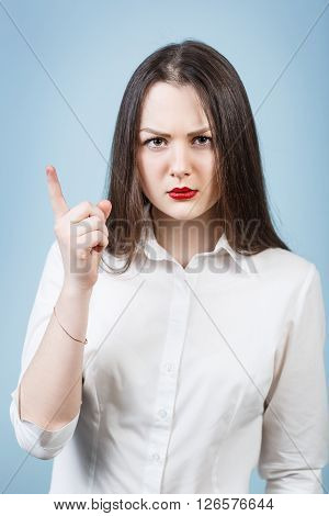 Young angry woman threaten finger on the blue background