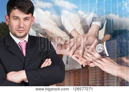 Businessman and business team showing unity with their hands together
