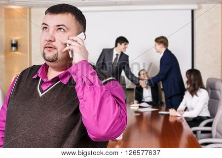 Businessman speak on the phone foreground and business people shaking hands, finishing up a meeting