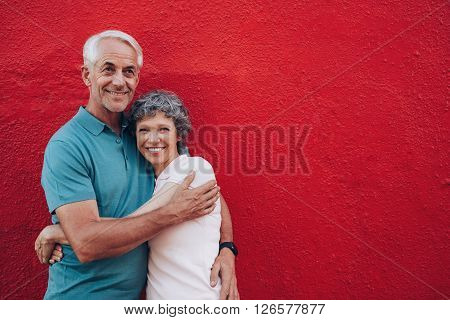 Affectionate Mature Couple Together On Red Background