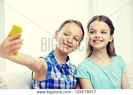 people, children, technology, friends and friendship concept - happy little girls sitting on sofa and taking selfie with smartphone at home