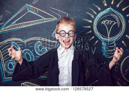 Little boy scientist in glasses cheerfully shouts