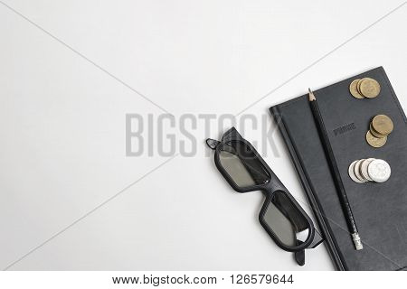 Flat lay of black notebook, pen, glasses and ruble coins on wooden surface with copy space on left side.