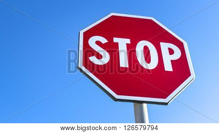 Forefront of a stop sign with a clear blue sky