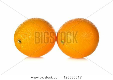 unpeeled whole ripe oranges on a white background