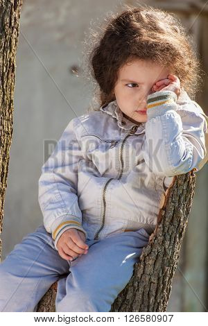 Portrait of sad baby girl sitting on tree stump