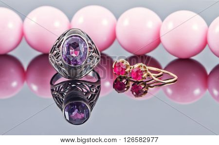 Silver ring with amethyst and gold earrings with a ruby on a background of pink beads
