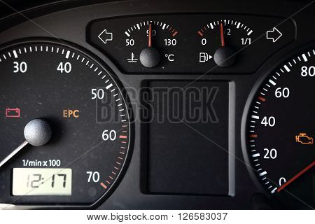 Black dashboard with clock revolution counter spedometer and smaller gauges