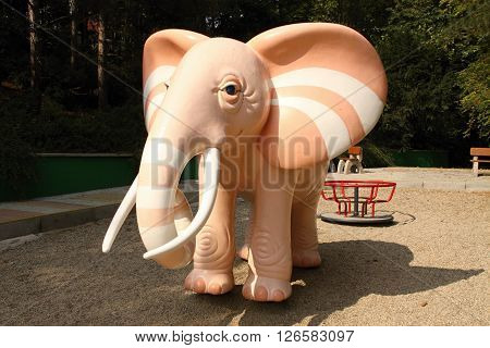 Pink or oragne scuplture of the elephant on the playground