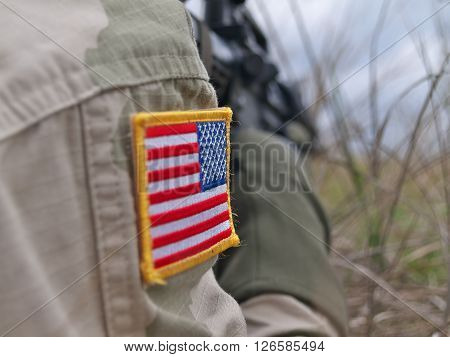 US Army soldier in action - flag patch closeup and rifle on the background