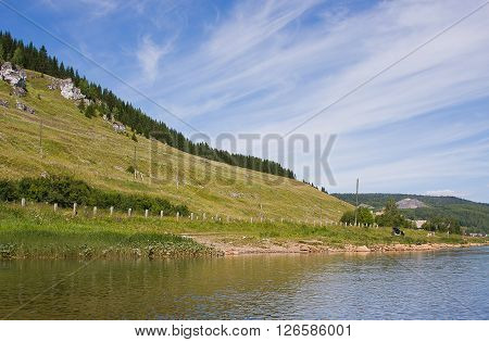 Beautiful Landscape On The Riverside With Rocks On A Hill