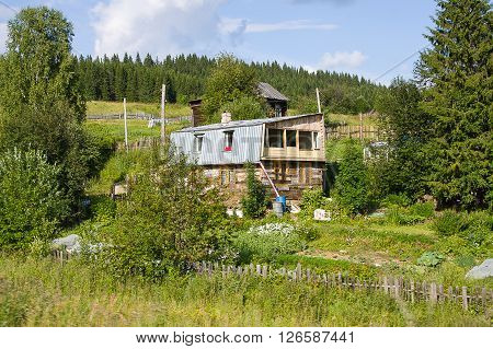 wooden house in a village sunny summer day, Russia