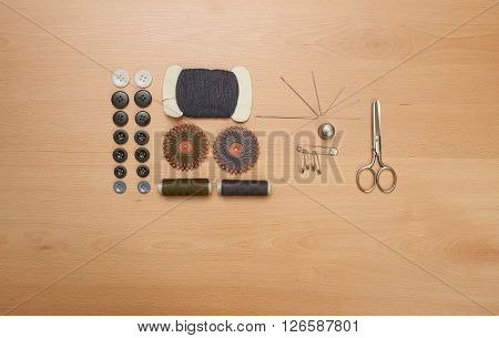 Sewing kit. Scissors bobbins with thread and needles on wooden table