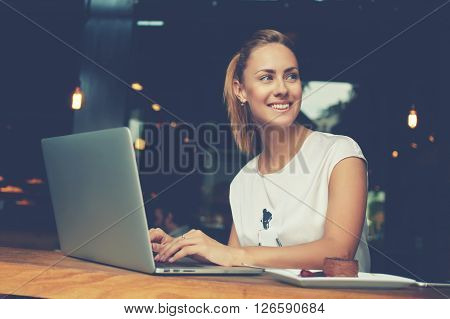 Gorgeous cheerful woman freelancer with good mood using laptop computer for distance work during lunch in cafe bar attractive female with beautiful smile sitting with portable net-book in coffee shop