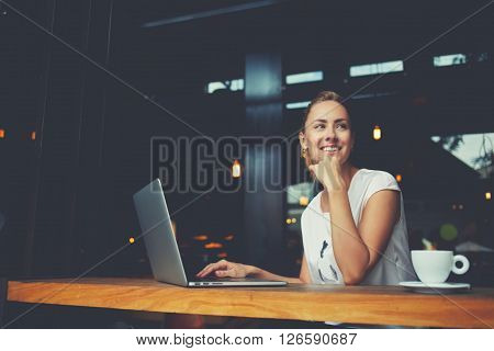 Young female with cute smile sitting with portable net-book in modern coffee shop interior during recreation time charming happy woman student using laptop computer to prepare for the course work