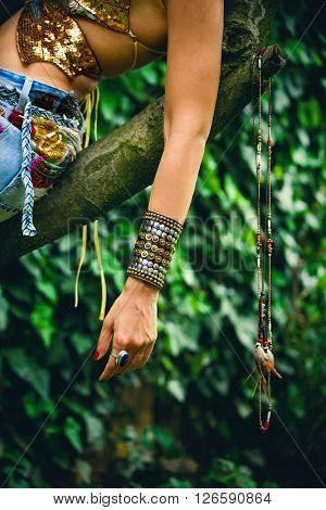 woman hand with massive metal bracelet and ring outdoor shot in garden on tree closeup