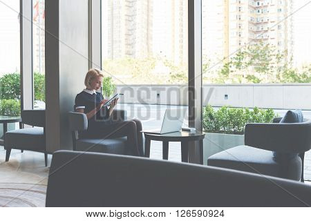 Female student is checking e-mail on digital tablet while is waiting file download on laptop computer. Businesswoman is ordering on-line car via touch pad while is sitting with net-book in cafe