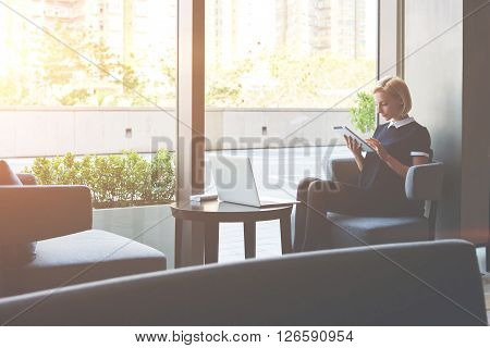 Female student is reading electronic book on touch pad after on-line training on laptop computer while is sitting in coffee shop. Young woman manager is using digital tablet for searching resumes