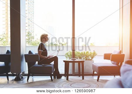 Young successful businesswoman is thinking about work ideas while is sitting with laptop computer on a knees in modern restaurant interior against window with copy space for your advertising content