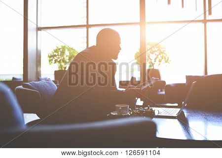 Silhouette of a skilled businessman is working on the idea of expanding his company while is sitting till late in office with net-book and touch pad. Young male entrepreneur is using digital tablet