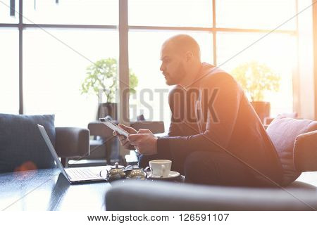 Male chain stores owner is checking invoices on touch pad and laptop computerwhile is sitting in modern interior. Man financier is analyzes financial transactions by using digital tablet and net-book